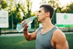 Male athlete drinks water on outdoor workout. Male athlete drinks water on outdoor fitness workout. Strong sportsman on sport training in park Stock Photography