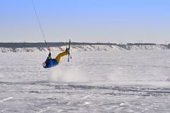 A male athlete engaged in snow kiting on the ice of a large snowy lake. He performs the jump. Winter sunny frosty day.  Royalty Free Stock Photos