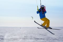 A male athlete engaged in snow kiting on the ice of a large snowy lake. He performs the jump. Winter sunny frosty day. Close-up Royalty Free Stock Photos