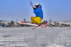 A male athlete engaged in snow kiting on the ice of a large snowy lake. He performs the jump. Winter sunny frosty day. Close-up Stock Images