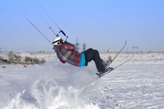 A male athlete engaged in snow kiting on the ice of a large snowy lake. He performs the jump. Winter sunny frosty day. Close-up Royalty Free Stock Photo