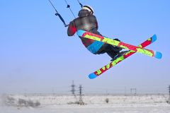A male athlete engaged in snow kiting on the ice of a large snowy lake. He performs the jump. Winter sunny frosty day. Close-up Stock Photography