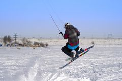 A male athlete engaged in snow kiting on the ice of a large snowy lake. He performs the jump. Winter sunny frosty day. Close-up Royalty Free Stock Image