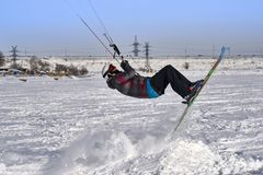 A male athlete engaged in snow kiting on the ice of a large snowy lake. He performs the jump. Winter sunny frosty day. Close-up.  Royalty Free Stock Images