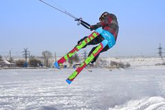 A male athlete engaged in snow kiting on the ice of a large snowy lake. He performs the jump. Winter sunny frosty day. Close-up Stock Image