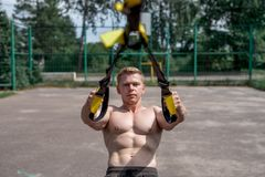 Male athlete is an excellent training, in the city in the summer, trx training, feel your strength and balance. Motivation, tanned skin. Exercise of the muscle Royalty Free Stock Photos