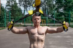 Male athlete is an excellent training, in city in the summer, trx training, feel your strength and balance, motivation Stock Images