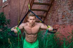 Male athlete excellent training trx, fresh air nature summer city, tanned skin, feel your strength, motivation, close-up. Male athlete excellent training trx Royalty Free Stock Images