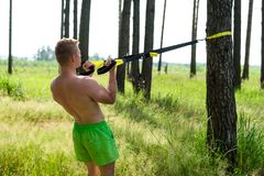 Male athlete excellent training trx, fresh air nature in summer forest, feel your strength, motivation, close-up. Male athlete excellent training trx, fresh air Stock Photos