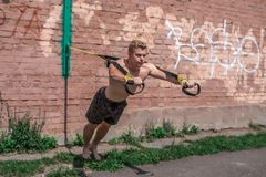 Male athlete is an excellent workout full length, wrung out in nature in city in summer, trx training, feel your. Male athlete is an excellent workout full Stock Photo