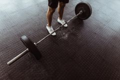 Male athlete exercising with heavy weights. At gym.  High angle view of man feet with barbell on gym floor Royalty Free Stock Photo