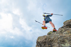 Male athlete falls from rocky ledges and practical training. Male athlete falls over a cliff with sticks while practical training at the mountain trail Royalty Free Stock Photography