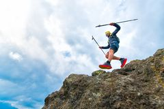 Male athlete falls from rocky ledges and practical training at t. Male athlete falls over a cliff with sticks while practical training at the mountain trail Stock Images