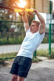 A male athlete goes in for sports in the open air. Muscular arms. Blonde in a white T-shirt. Lifestyle of the. A male athlete trains hinges, city in fresh air Royalty Free Stock Photos