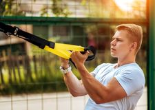 A male athlete goes in for sports in the open air. Muscular arms. Blonde in a white T-shirt. Lifestyle of the. A male athlete goes in for sports in the open air Royalty Free Stock Photos