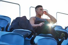 Male athlete with gym bag listening to music before work out. Montreal, Quebec, Canada Stock Image