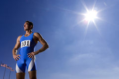 Male athlete with hands on hips, low angle view (sun flare) Stock Image