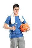 Male athlete holding bottle od water and a basketball Royalty Free Stock Photos