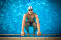 Male athlete holding on edge of swimming pool and preparing to s. Young male athlete holding on edge of swimming pool and preparing to swim Royalty Free Stock Photos