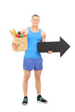 Male athlete holding a grocery bag and an arrow Stock Images