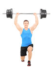 Male athlete holding a heavy weight and doing lunges Royalty Free Stock Image