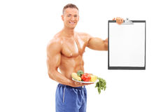 Male athlete holding a plate with vegetables Stock Images