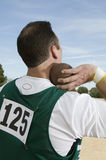 Male Athlete Holding A Shot Put. Rear view of male athlete ready to throw shot put Royalty Free Stock Image