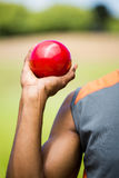 Male athlete holding shot put ball. Mid section of male athlete holding short put ball in a stadium Stock Photography