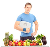 Male athlete holding a weight scale behind a table full of food Royalty Free Stock Images