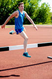 Male athlete jumping hurdle Royalty Free Stock Images