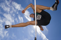Male athlete jumping over hurdle, view from below Stock Images
