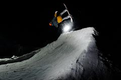 Male athlete jumping on snowboard, against the background of dark sky. Male athlete in ski outfit jumping on snowboard, raising snowy snowstorm, against the Stock Photos