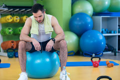 Male athlete kneeling down by dumbbells toweling sweat of his brow. Royalty Free Stock Image