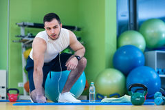 Male athlete kneeling down by dumbbells toweling sweat of his brow. Royalty Free Stock Photography