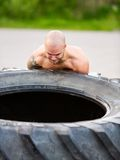 Male Athlete Lifting Truck Tire Royalty Free Stock Photos