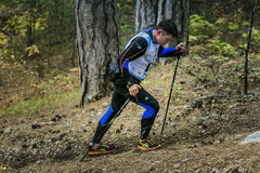 Male athlete middle-aged rises along a forest trail with nordic walking poles. Yalta, Russia - November 2, 2015: male athlete goes to mountain behind him a small Stock Photography