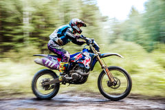 Male athlete motorcycle racer rides in woods Royalty Free Stock Photo