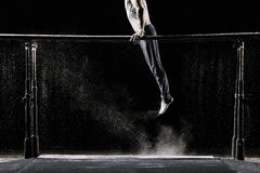 Male athlete performing handstand on gymnastic parallel bars with talcum powder.  on black. Royalty Free Stock Photography
