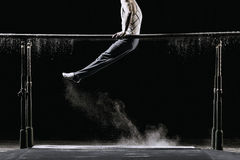 Male athlete performing handstand on gymnastic parallel bars with talcum powder. Isolated on black. Stock Images