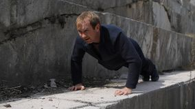 Male athlete performs push-UPS on the floor in a marble quarry