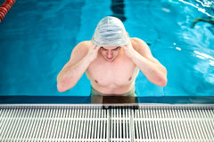 Male athlete, polo player getting ready for swimming. Swimmer wearing rubber cap. Male athlete, polo player getting ready for swimming. Swimmer wearing cap Stock Photography