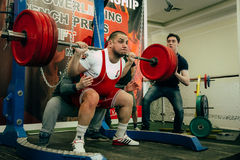 Male athlete of powerlifter squats barbell Royalty Free Stock Photo