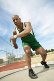 Male Athlete Preparing To Throw Discus. Full length of African American men preparing to throw discus as far as possible Stock Photography