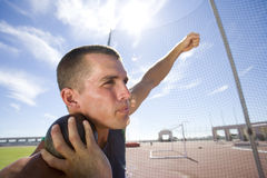 Male athlete preparing to throw shot put ball, low angle view (lens flare) Royalty Free Stock Photo