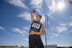 Male athlete preparing to throw shot put ball, low angle view (lens flare) Royalty Free Stock Images