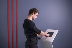 Athlete regulating intensity of ems electro muscular stimulation machine. Male athlete pushing on screen on ems machine regulating intensity Royalty Free Stock Photo