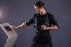 Athlete regulating intensity of ems electro muscular stimulation machine. Male athlete pushing on screen on ems machine regulating intensity Stock Image