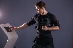 Athlete regulating intensity of ems electro muscular stimulation machine Stock Image