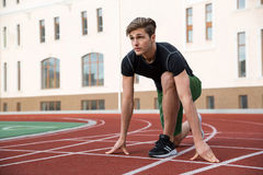Male athlete ready to run on running track. Picture of handsome young male athlete ready to run on running track outdoors. Looking aside Royalty Free Stock Image