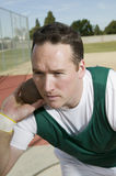 Male Athlete Ready To Throw Shot Put. On track and field Stock Photography